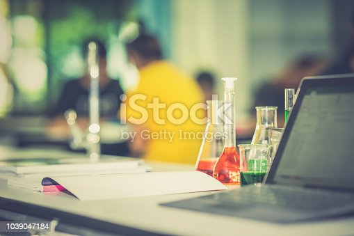 Glassware chemistry science laboratory on table and blurred tablet on blurred student in classroom