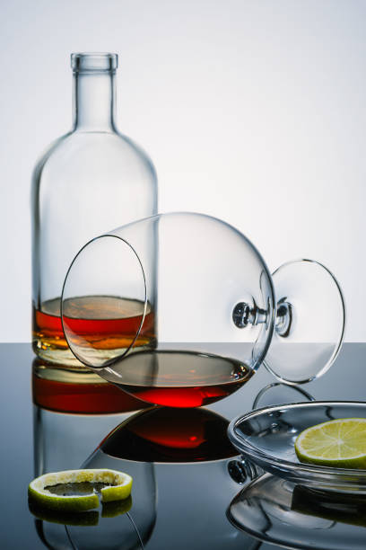 Cтоковое фото Glasswares winh the alcohol remains, pieces and a peel of a lime on the reflecting surface