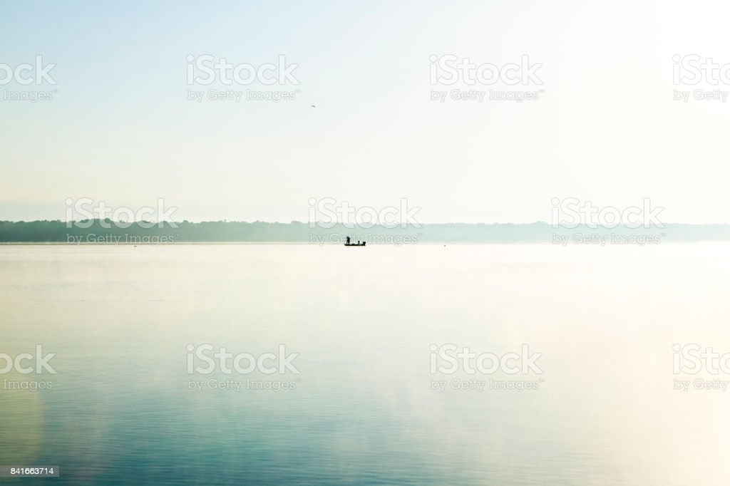 Glassy calm, misty morning lake and fishing boat stock photo