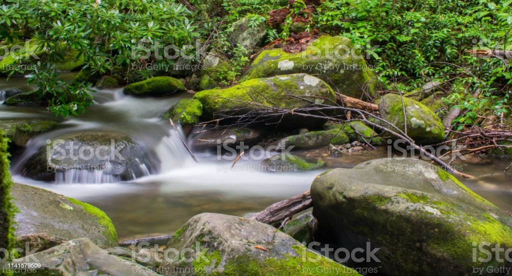 Glassy water flows over rocks stock photo