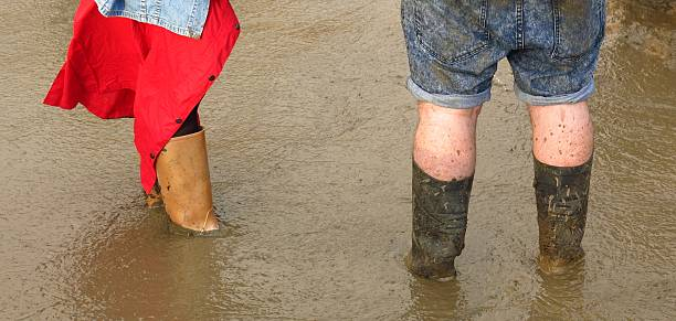 Glastonbury festival fans ankle deep in mud in Wellies stock photo