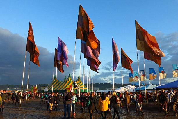 Glastonbury festival flags crowds mud tents stock photo