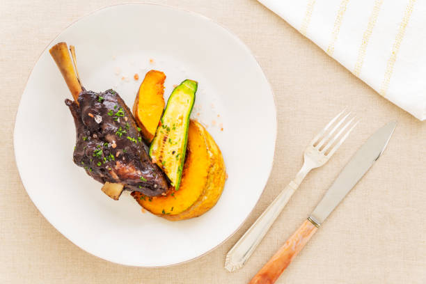 Glazed braised lamb shank with pumpkin and zucchini in a beige plate on a beige tablecloth aside a fork, a knife and a white napkin. Flat lay top view. stock photo