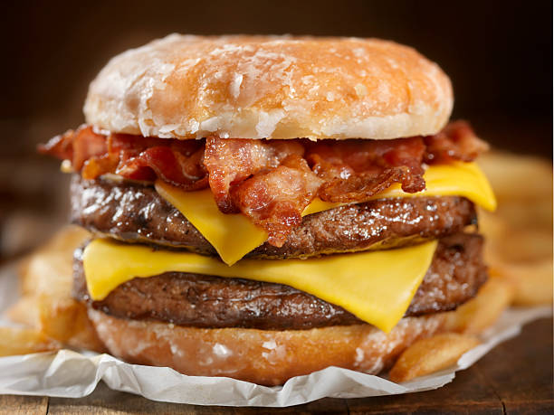 Glazed Donut Bacon Cheeseburger The Burger lovers brunch! It sounds like an odd combination but it tastes as good as it looks. It has also been a huge hit this summer across the US and Canada at Carnivals, State Fairs and even a few Food Trucks.-Photographed on Hasselblad H3D2-39mb Camera bacon cheeseburger stock pictures, royalty-free photos & images