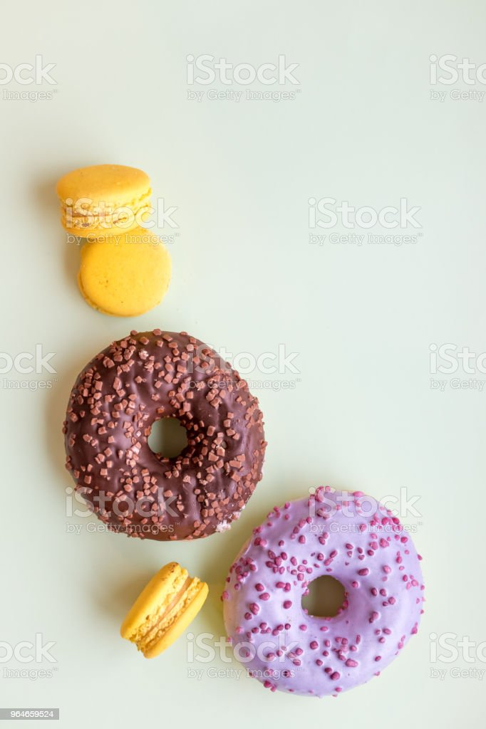 Glazed donuts and macaroons. Sweet dessert isolated on soft green background. Cakes with buttercream. lemon, yellow macaron cookies.Pop art color style.Selective focus. Copy space royalty-free stock photo