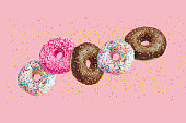 istock glazed doughnuts in motion falling on pink background with colorful sprinkles 1158583088
