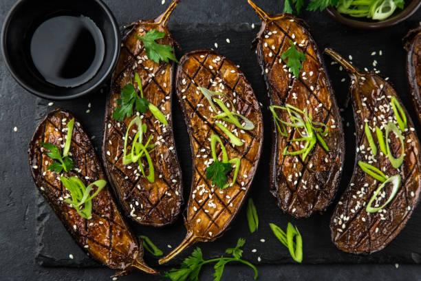 glazed grilled eggplants served with sesame seeds and green onion stock photo