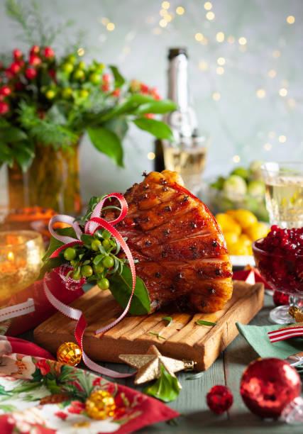 Glasierter Schinkenbraten mit Nelken, Sekt und traditionelle Gemüsegerichte zum Weihnachtsessen. – Foto