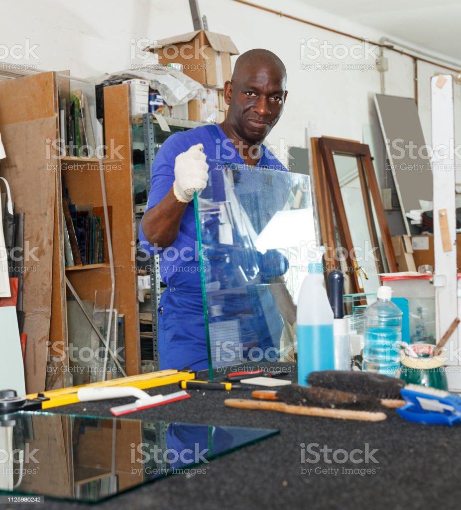 African American glazier controlling quality of glass product in...