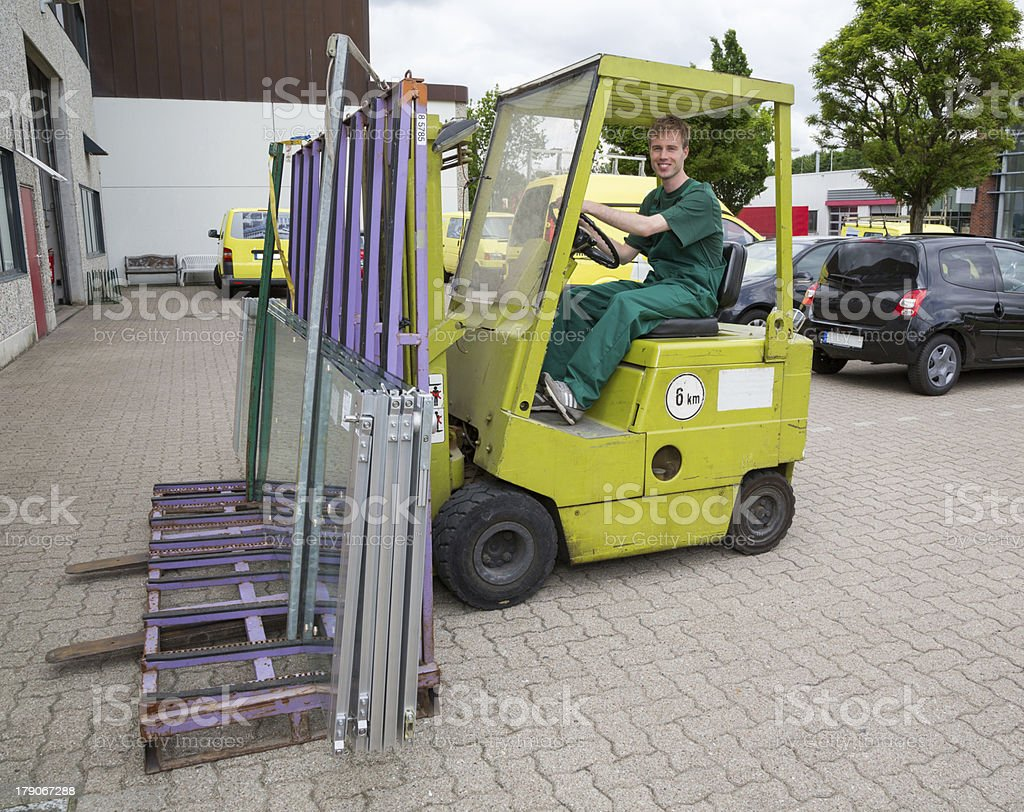 Glazier operating a forklift truck with panes of glass royalty-free stock photo