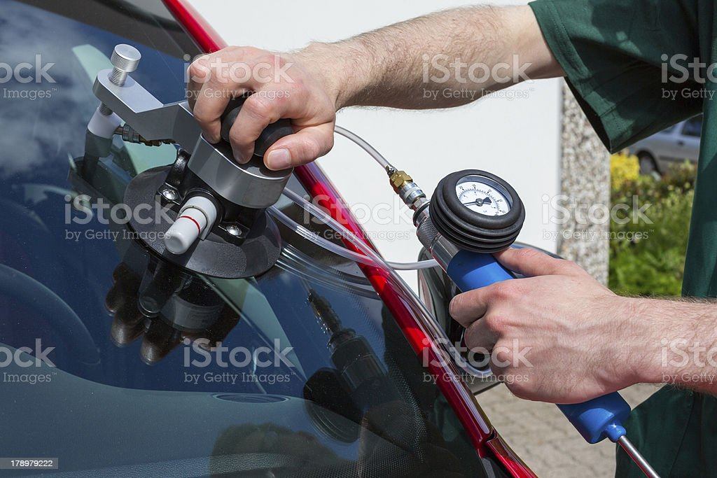 Glazier repairing windscreen after stone chipping damage royalty-free stock photo