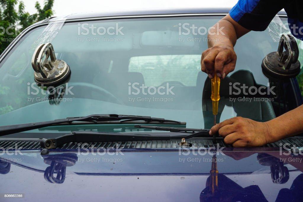 Glazier using tools repairing to fix crack broken windshield on the front window glass. – zdjęcie