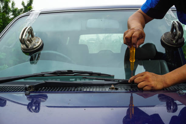 Glazier using tools repairing to fix crack broken windshield on the front window glass. Glazier using tools repairing to fix crack broken windshield on the front window glass of the machine car accident. replacement stock pictures, royalty-free photos & images