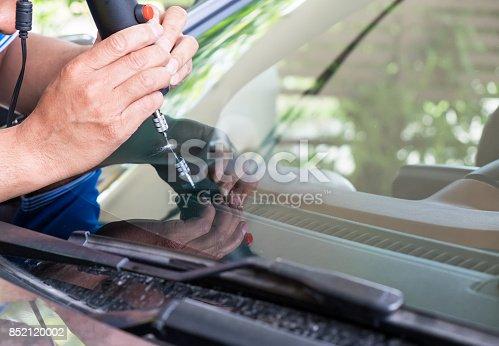 Glazier using tools repairing to fix crack windshield