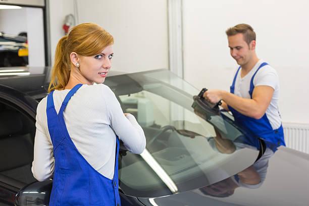glaziers in der garage installieren oder windschutzscheibe auf auto-windschutzscheibe - fensterbauer stock-fotos und bilder