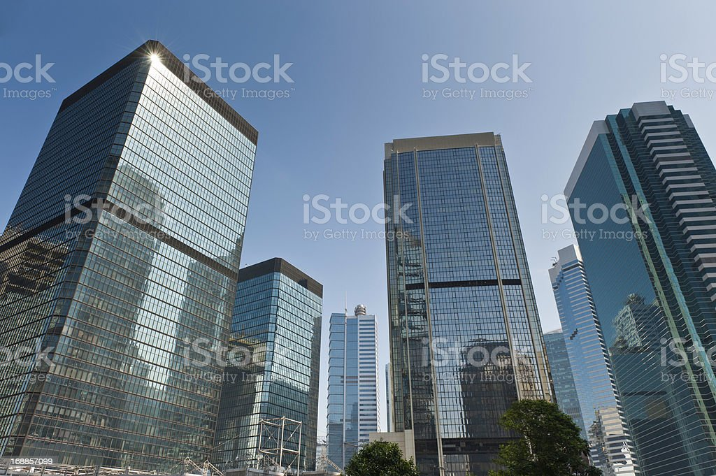 bf361228582a Gleaming glass business skyscrapers soaring into blue sky - Stock image .