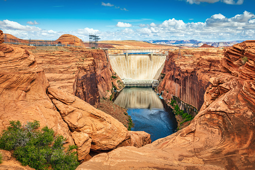 Glen Canyon Dam on Colorado River and Power Station under blue summer cloudscape. Glen Canyon Dam is a concrete arch-gravity dam on the Colorado River and forms Lake Powell, one of the largest man-made reservoirs in the USA. Glen Canyon Dam, Page, Northern Arizona, USA, North America