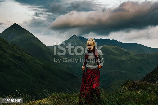 Woman in scottish kilt above Glen Shiel, in the Highlands of Scotland. View is west towards The Saddle and Faochag.