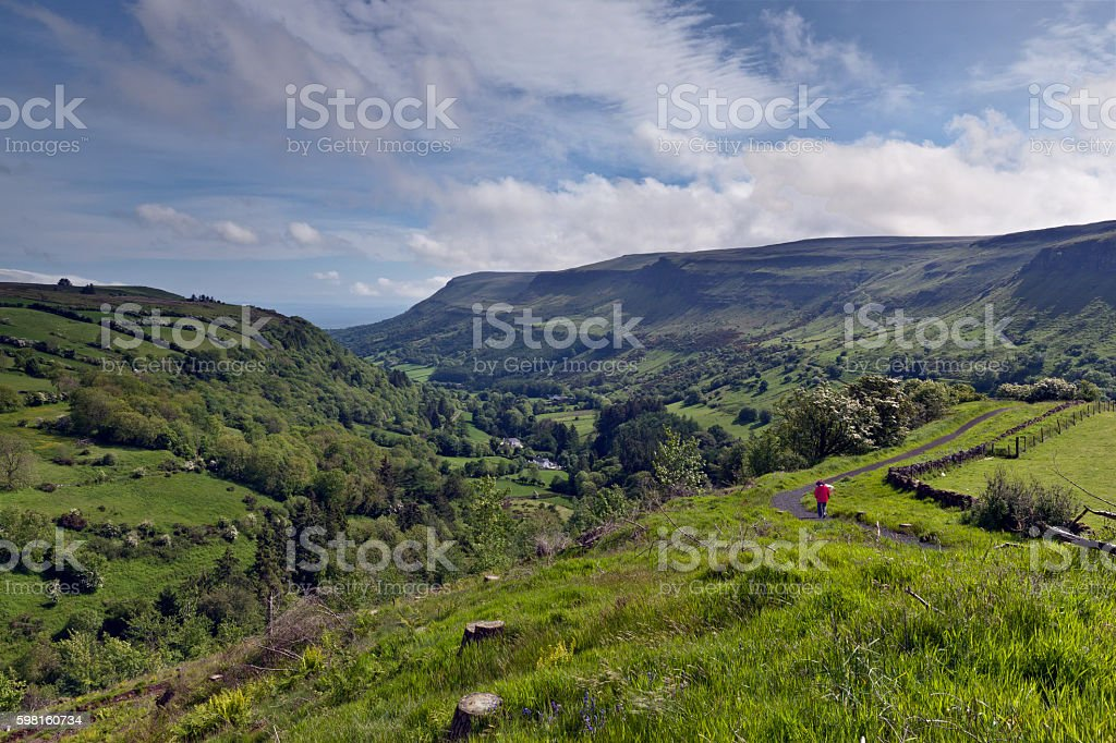 Glenariff Spring with human figure Here is the view of Glenariff from the Glenariff Forest Park on a June morning.  An anonymous human figure walking away provides scale and interest.  Glenariff is a valley of County Antrim, Northern Ireland.  Known for lush farmland, this glacially carved glen has a mouth on the North Channel of the Irish Sea at the town of Waterfoot.   County Antrim Stock Photo