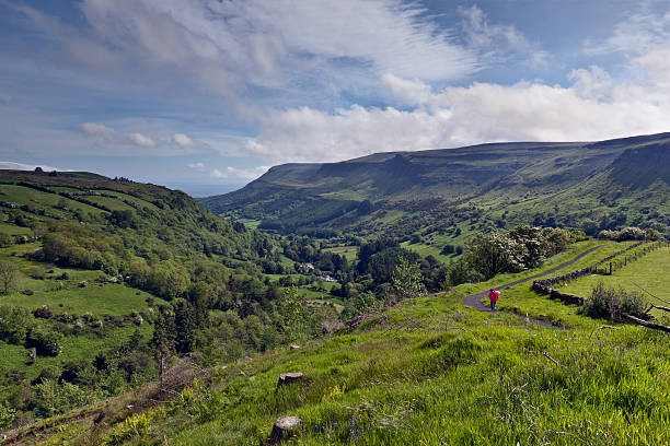 Glenariff Spring with human figure Here is the view of Glenariff from the Glenariff Forest Park on a June morning.  An anonymous human figure walking away provides scale and interest.  Glenariff is a valley of County Antrim, Northern Ireland.  Known for lush farmland, this glacially carved glen has a mouth on the North Channel of the Irish Sea at the town of Waterfoot.   michael stephen wills glenariff stock pictures, royalty-free photos & images