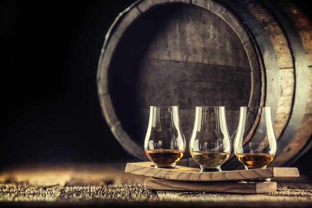 Glencairn whiskey tasting cups on a wooden serving, with a whisky barrel in the dark background stock photo