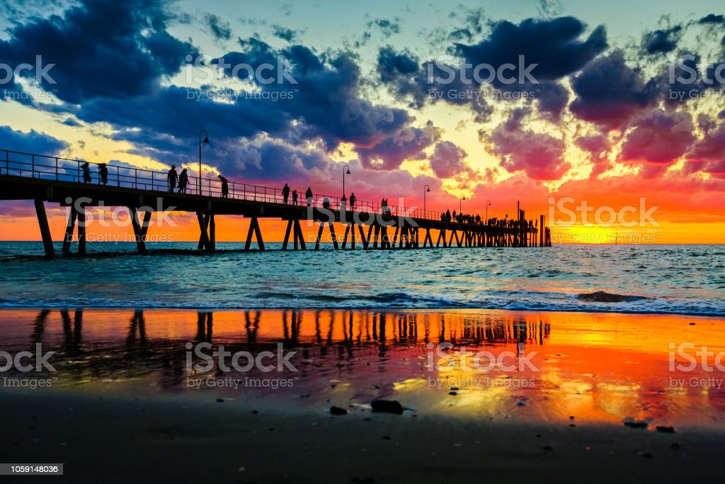 Glenelg jetty with people at sunset sky stock photo