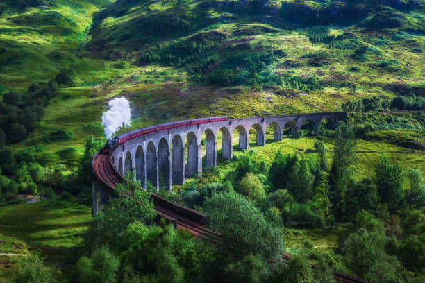 Glenfinnan Railway Viaduct in Scotland with a steam train Glenfinnan Railway Viaduct in Scotland with the Jacobite steam train passing over. Artistic vintage style processing. railway bridge stock pictures, royalty-free photos & images