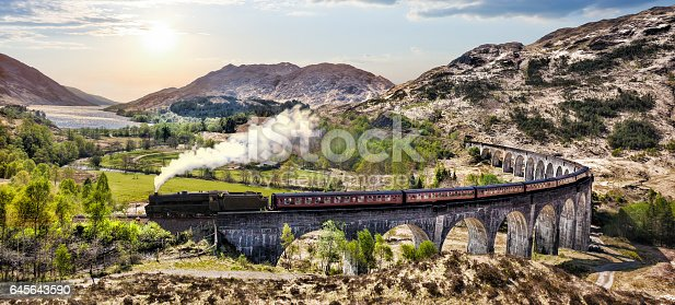 istock Glenfinnan Railway Viaduct in Scotland with the Jacobite steam train against sunset over lake 645643590