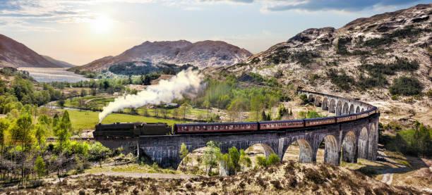Glenfinnan Eisenbahnviadukt in Schottland mit dem Jacobite Dampfzug gegen Sonnenuntergang über See – Foto