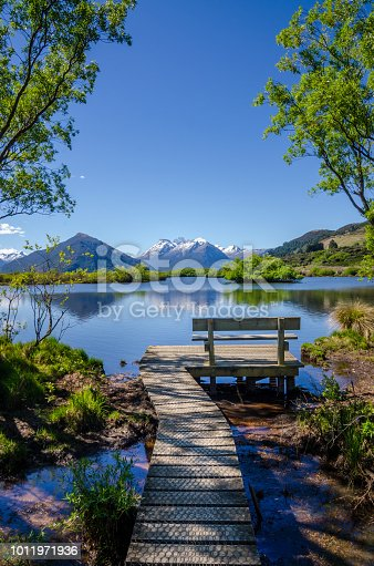Tranquil scene at Glenorchy, New Zealand with bench and footpath visible at the at the lake.