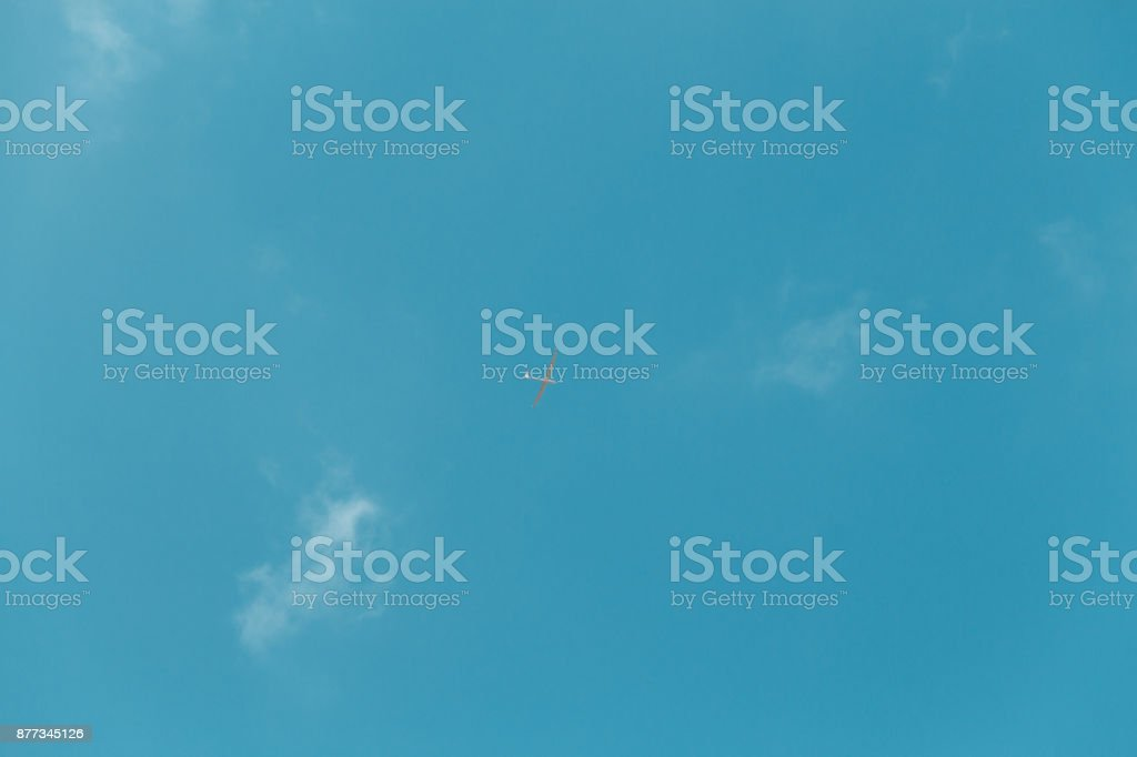 Glider gliding in blue sky from below stock photo
