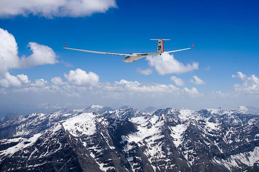 Glider in flight over mountains