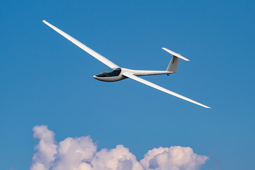 Glider plane flying in the cloudy sky