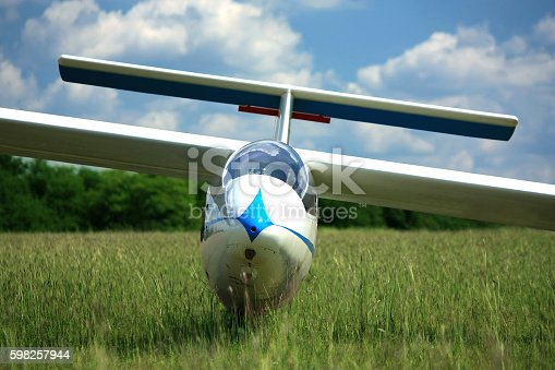 Blue white glider plane on airport grass