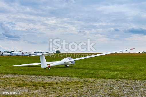 Glider plane standing on grass airport runway with dramatic sky background.