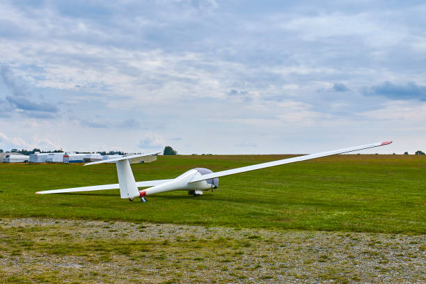 Glider plane standing on grass airport runway with dramatic sky background. stock photo