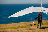 istock Glider ready to depart off a cliff the Pacific Ocean in California 1295055320