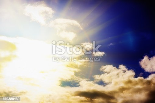 The sun dazzles as it emerges from behind  clouds on the left, radiating heavenly light.  Copy space on the cloud.
