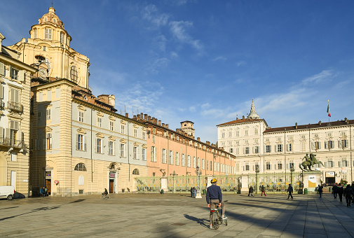 Glimpse of Piazza Castello square in the historic centre with the dome of Royal Church of San Lorenzo and the Royal Palace (Palazzo Reale) in a sunny day, Turin, Piedmont, Italy