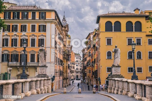 Rome, Italy, May 18 -- Through a cloudy sky the light of the sunset illuminates Ponte Sant'Angelo in Rome, near the Vatican district. In the background  Via del Banco di Santo Spirito, one of the oldest and most famous streets in Rome. Image in High Definition format.