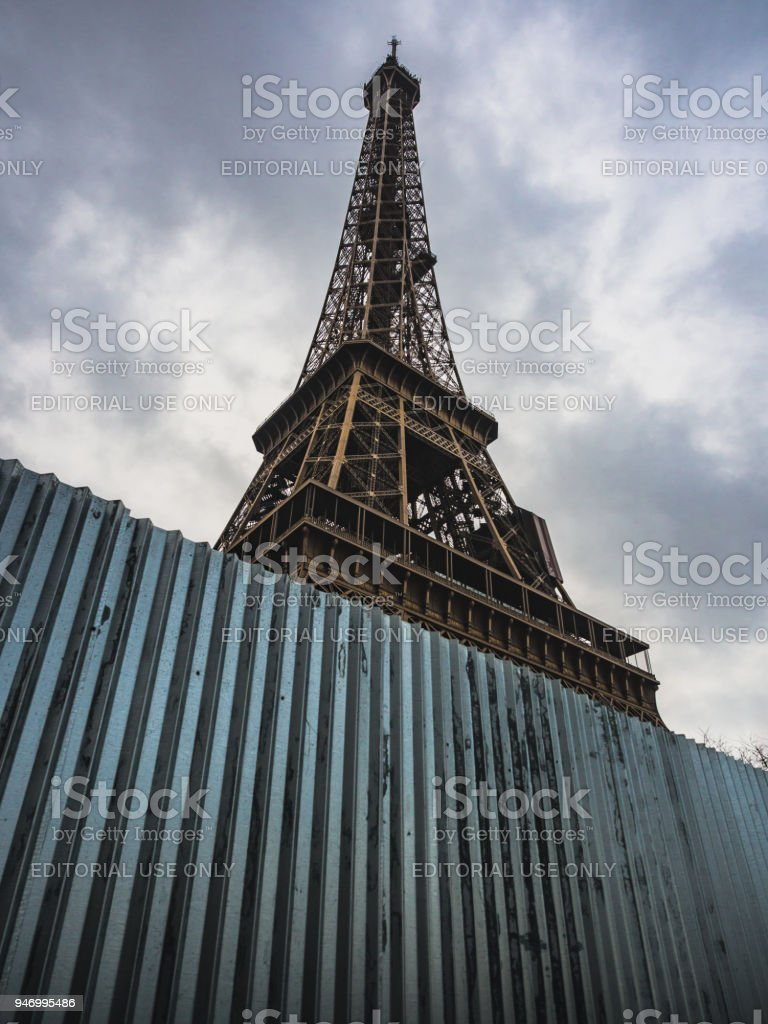 A glimpse of the Eiffel Tower and iron barriers to counteract any terrorist attacks. stock photo