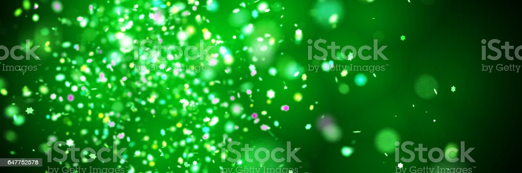 glitter banner - festive star-shaped colourful glitter with bokeh effect in front of a dark green background stock photo