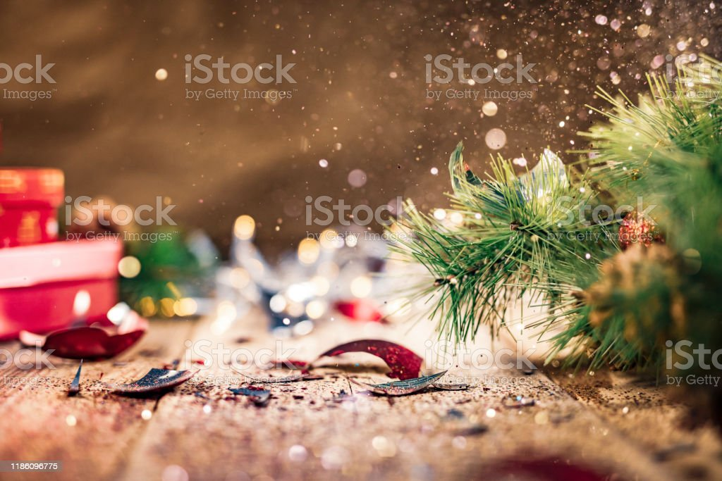Glitter being scattered over a broken Christmas ball Glitter being scattered over a broken red fragile Christmas bauble laying on the floor, crushed into pieces. Advent Stock Photo