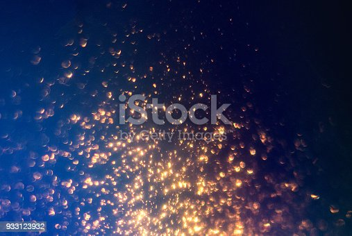 istock Glitter lights abstract background. Golden Sparkle stardust on blue and black defocused texture. 933123932
