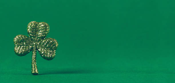 glitzer-kleeblatt auf grünem papierhintergrund. st patricks tag symbol. irische nationale ferienkonzept - st. patrick's day stock-fotos und bilder