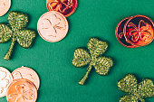 Glitter shamrocks and golden coins on green paper background. St Patricks day symbol. Irish National holiday concept. Horizontal