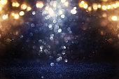 glitter vintage lights background. black, gold and blue. de-focused
