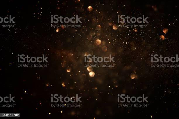 Photo of glitter vintage lights background. dark gold and black. de focused.