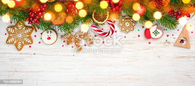 istock Glittered hristmas background, decorated holiday tree branches and gingerbread cookies 1044689084