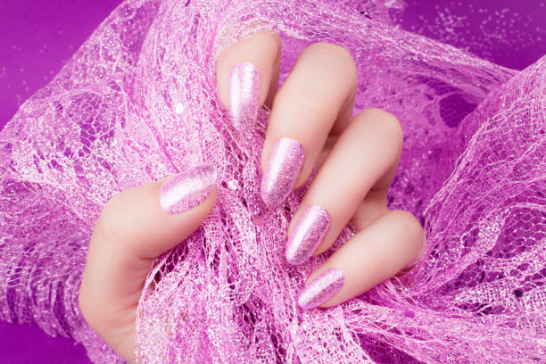 glittered pink nails manicure Female hand with glittered pink nails manicure is holding pink decoration on pink background. pink nail polish stock pictures, royalty-free photos & images